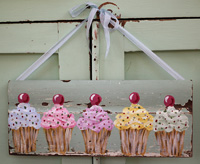 Cupcakes with cherries painted on old architectural salvage
