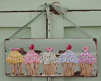 Cupcakes with assorted toppings painted on old architectural salvage